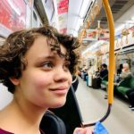 Young woman on train in Osaka health benefits of traveling abroad