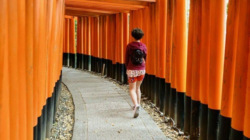Young woman walking in Inari shrine gates in Kyoto Japan
