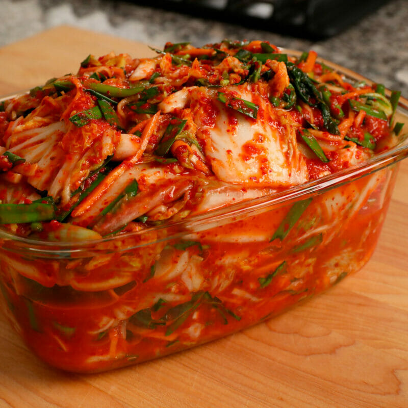 Homemade kimchi fermenting in a glass dish