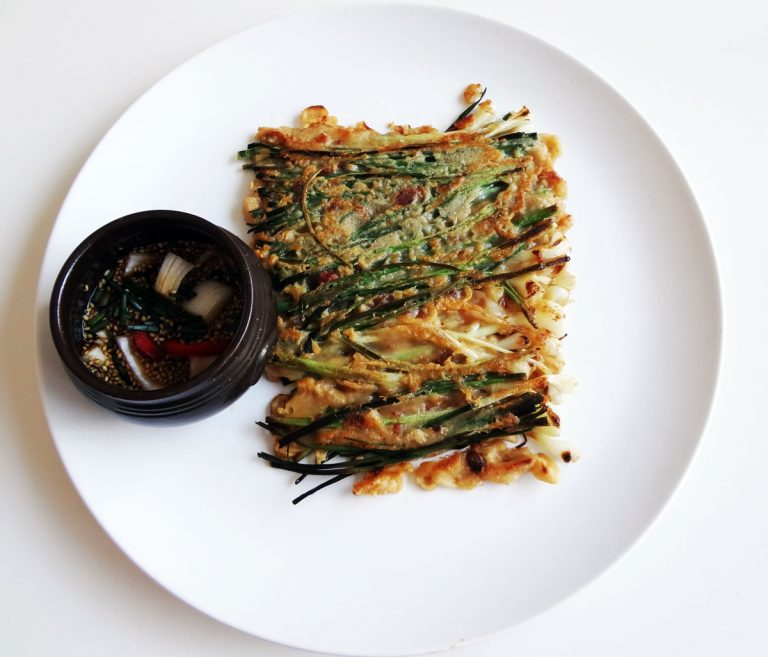 Pajeon green onion scallions pancake on white plate with dipping sauce