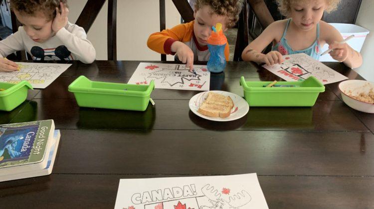 Three kids sitting at a dark brown kitchen table for homeschool