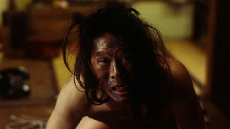 Screenshot of man crawling in Japanese movie Audition