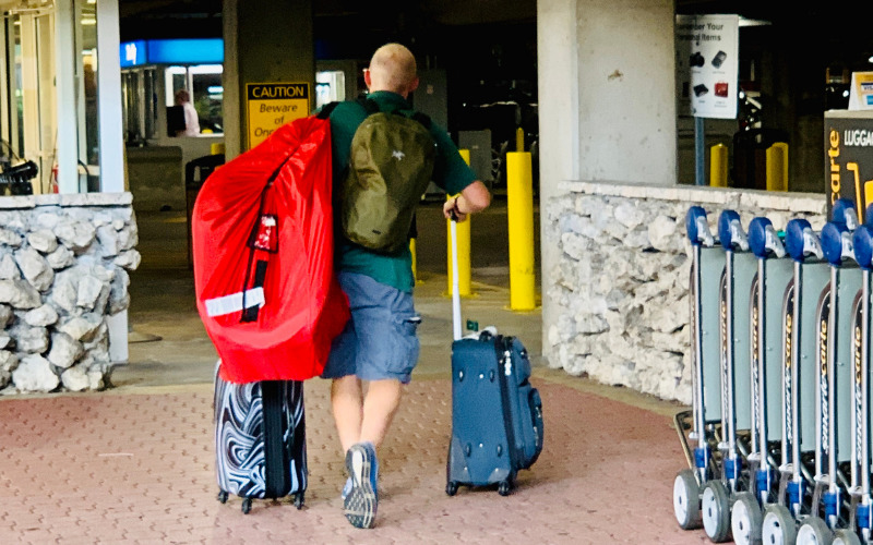 Man wheeling luggage carrying a red car seat travel bag cover