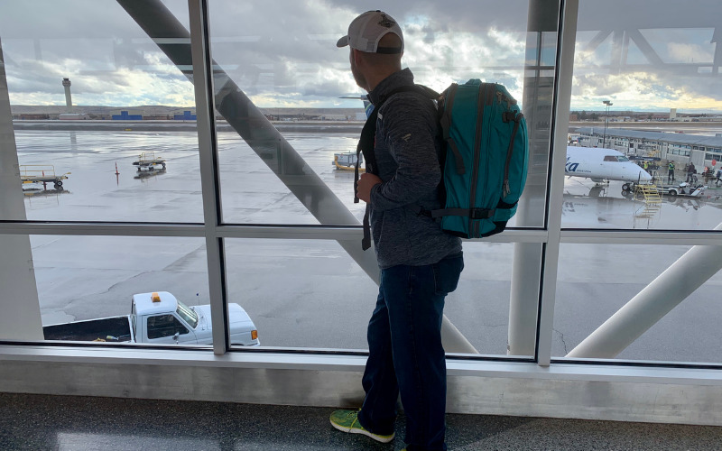 Man standing at airport with carry-on backpack