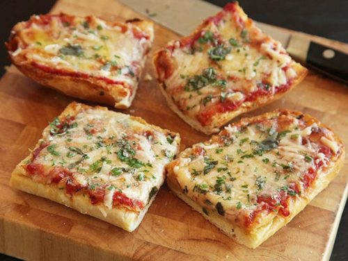 French bread pizza on a cutting board