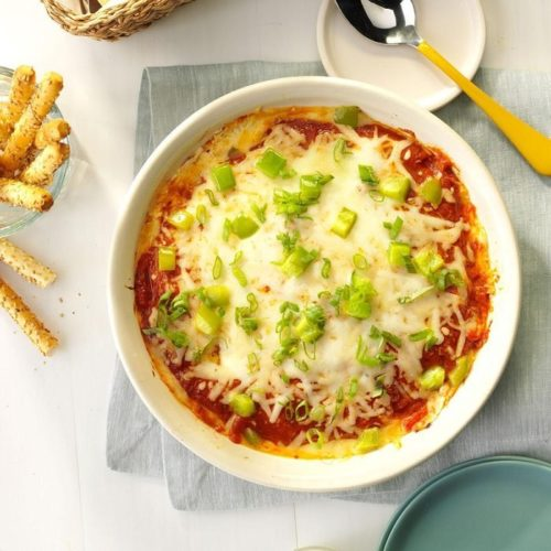 Hot pizza dip appetizer in white bowl on table with breadsticks
