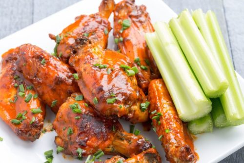 Slow cooker buffalo ranch chicken wings with celery on a white plate