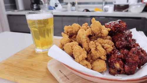 Korean fried chicken in a serving dish on a cutting board with beer